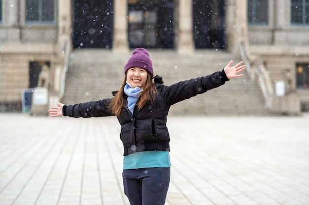 Azjatycka młoda kobieta gra na śniegu, gdy śnieg właśnie spadł, podróż i podekscytowany koncept, wełniany kapelusz ze scartem i płaszcz na zimę