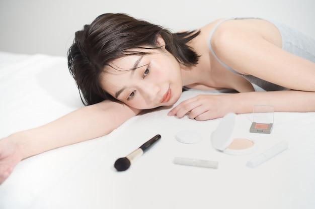 Azjatycka młoda kobieta i przedmioty kosmetyczne