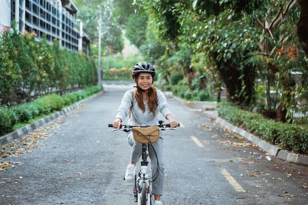 Azjatycka młoda kobieta idzie w hełmie do jazdy, składając rower