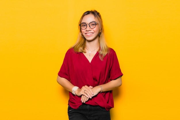 Azjatycka młoda kobieta jest ubranym okulary przeciwsłonecznych na kolor żółty ścianie