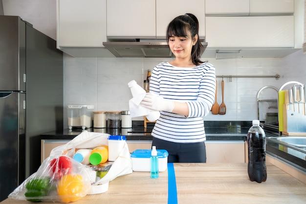 Azjatycka młoda kobieta kłaść produkty spożywcze na podzielonym stole i wyciera w dół