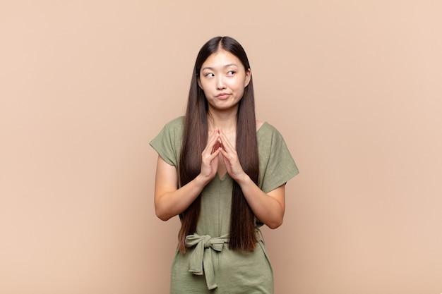 Azjatycka młoda kobieta knuje i spiskuje, myśli podstępne sztuczki i oszustwa, przebiegłość i zdradę