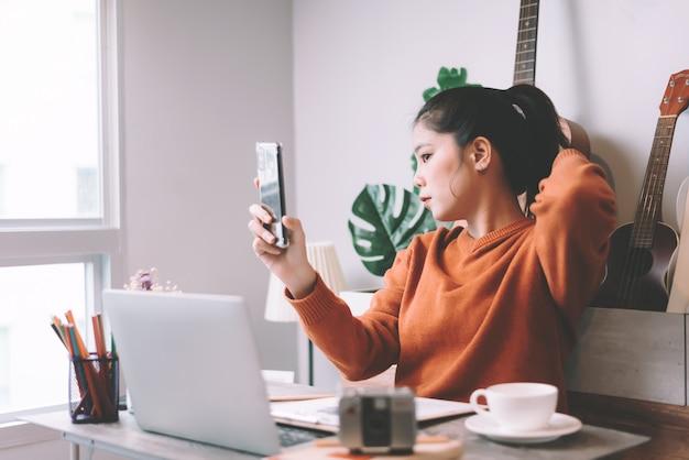 Azjatycka młoda kobieta kreatywnie pracuje na laptopie i selfie z smartphone w ranku - pracujący od domowego pojęcia