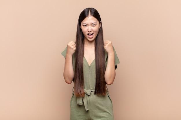 Azjatycka młoda kobieta krzyczy agresywnie z gniewnym wyrazem twarzy lub z zaciśniętymi pięściami świętując sukces