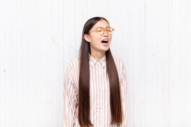 Azjatycka młoda kobieta krzyczy wściekle, krzyczy agresywnie, wygląda na zestresowaną i wściekłą