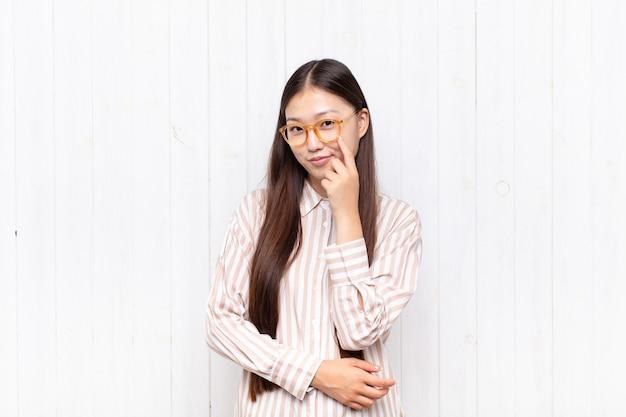 Azjatycka młoda kobieta ma na ciebie oko, nie ufa, obserwuje i zachowuje czujność i czujność