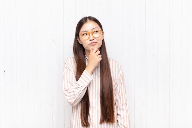 Azjatycka młoda kobieta myśli, czuje się niepewna i zdezorientowana, ma różne opcje, zastanawia się, jaką decyzję podjąć