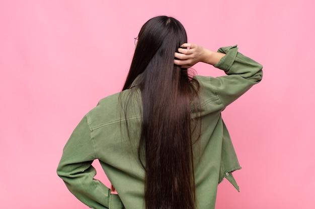 Azjatycka młoda kobieta myśli lub wątpi, drapiąc głowę na białym tle