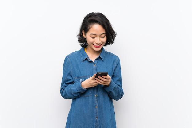 Azjatycka młoda kobieta nad odosobnioną biel ścianą wysyła wiadomość z wiszącą ozdobą