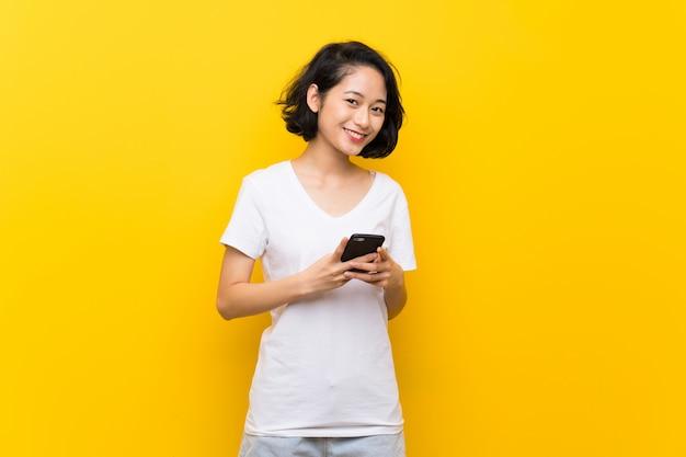 Azjatycka młoda kobieta nad odosobnioną kolor żółty ścianą wysyła wiadomość z wiszącą ozdobą
