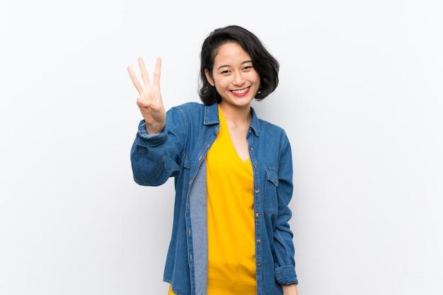 Azjatycka młoda kobieta nad odosobnionym białym tłem szczęśliwym i liczy trzy z palcami