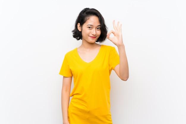 Azjatycka młoda kobieta nad odosobnionym bielem pokazuje ok znaka z palcami