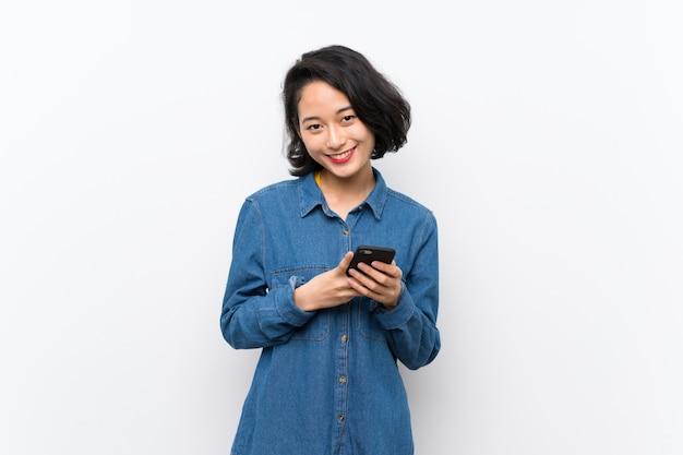 Azjatycka młoda kobieta nad odosobnionym bielem wysyła wiadomość z wiszącą ozdobą