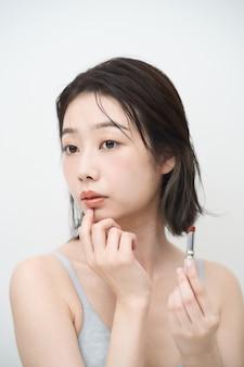 Azjatycka młoda kobieta nakłada szminkę na usta