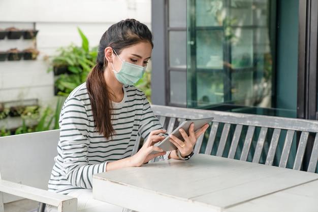 Azjatycka młoda kobieta nosząca maskę medyczną w celu ochrony przed koronawirusem lub chorobą covid-19 podczas używania tabletu na zewnątrz