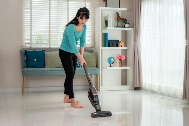 Azjatycka młoda kobieta nosząca przypadkowe ubrania czyści podłogę domu w salonie za pomocą odkurzacza w domu podczas pobytu w domu, korzystając z wolnego czasu na temat codziennych czynności porządkowych.