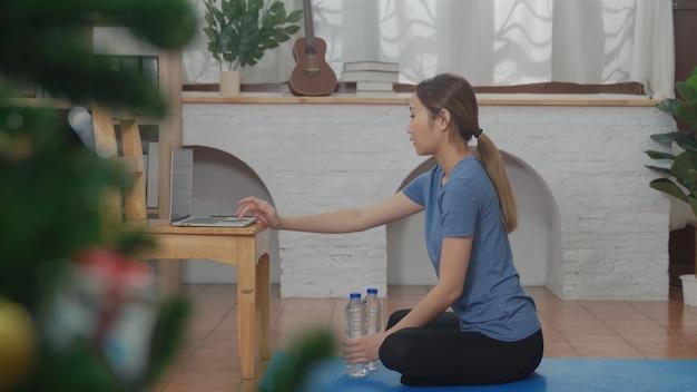 Azjatycka młoda kobieta ogląda samouczek online, ucząc się za pomocą laptopa do ćwiczeń w salonie w domu