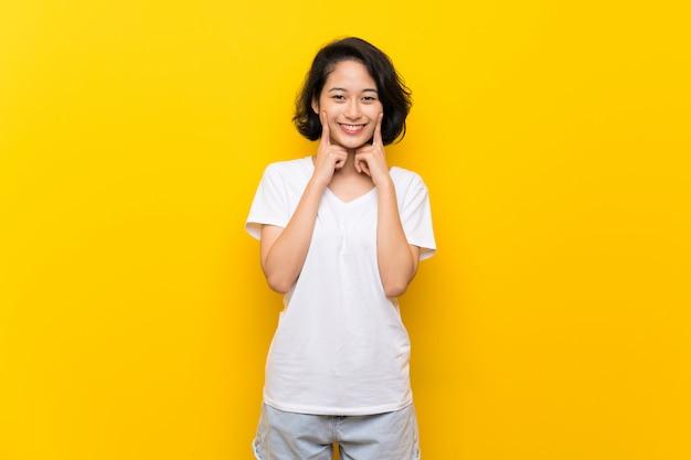 Azjatycka młoda kobieta ono uśmiecha się z odosobnioną żółtą ścianą z szczęśliwym i przyjemnym wyrażeniem