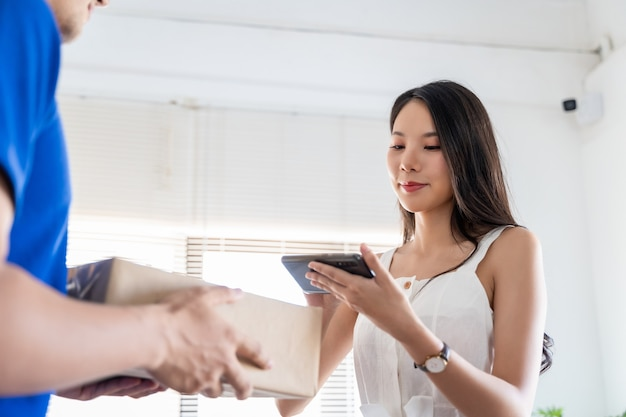 Azjatycka młoda kobieta otrzymująca pakiet od człowieka dostawy. uśmiechnięty młody dostawca trzymający karton, podczas gdy piękna młoda kobieta umieszcza podpis w schowku