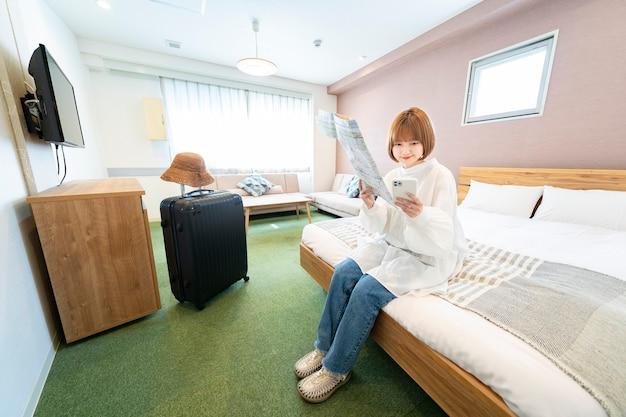 Azjatycka młoda kobieta patrząc na mapę i smartfon w pokoju hotelowym