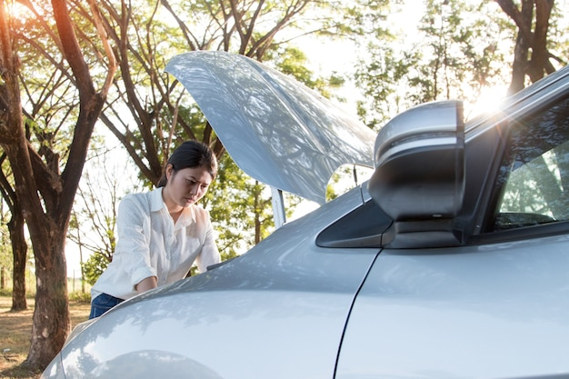 Azjatycka młoda kobieta patrzeje otwarcie kapiszon i dzwoni przy łamanym puszka samochodowym silnikiem na ulicie i otwiera