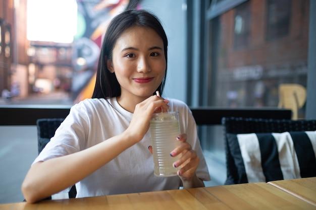 Azjatycka młoda kobieta pije lemoniadę w kawiarni na świeżym powietrzu i uśmiecha się