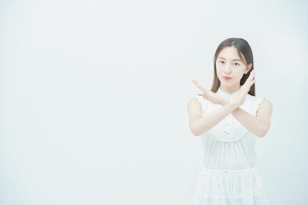 Azjatycka młoda kobieta robi znak krzyża obiema rękami