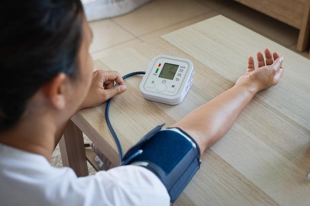 Azjatycka młoda kobieta samodzielnie w domu sprawdza ciśnienie krwi i tętno cyfrowym manometrem. pojęcie zdrowia i medycyny.