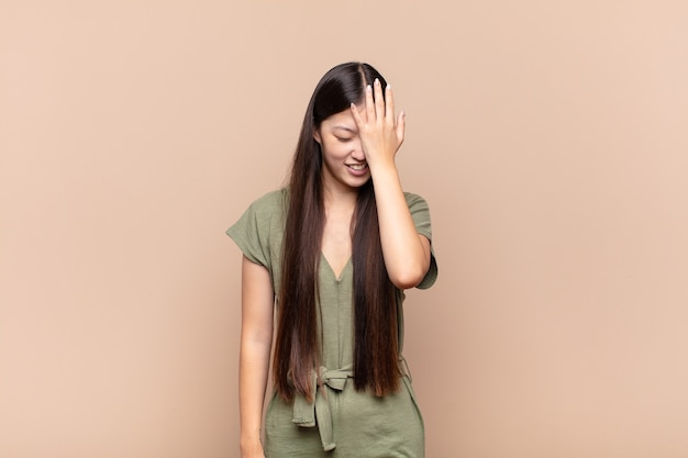 Azjatycka młoda kobieta śmiejąca się i uderzająca w czoło, jakby mówiła o! zapomniałem, czy to był głupi błąd