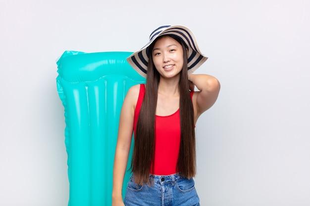 Azjatycka młoda kobieta śmiejąca się wesoło i pewnie z niezobowiązującym, szczęśliwym, przyjaznym uśmiechem