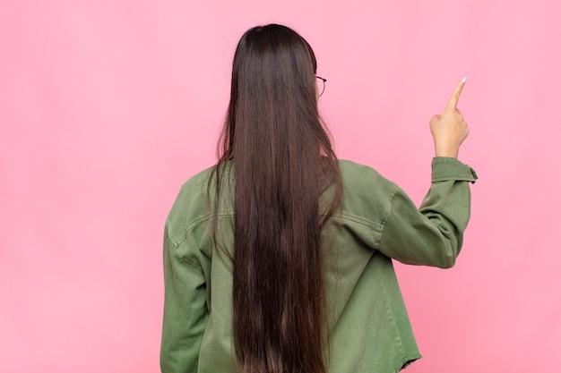 Azjatycka młoda kobieta stoi i wskazuje