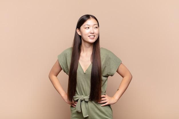 Azjatycka młoda kobieta szuka na białym tle szczęśliwy, wesoły i pewny siebie