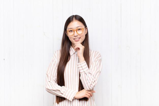 Azjatycka młoda kobieta szuka szczęśliwa i uśmiechnięta ręką na brodzie na białym tle