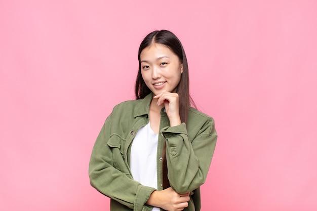 Azjatycka młoda kobieta szuka szczęśliwa i uśmiechnięta ręką na brodzie
