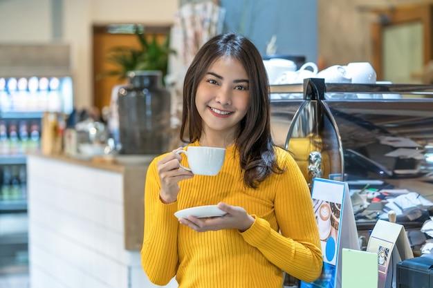 Azjatycka młoda kobieta trzymająca filiżankę kawy w nowoczesnej kawiarni lub przestrzeni coworkingowej