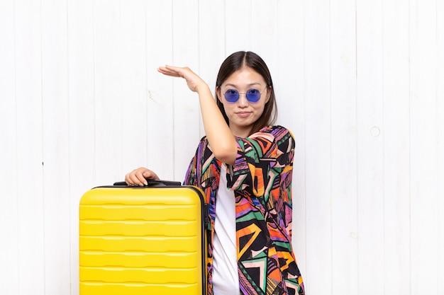 Azjatycka młoda kobieta trzymająca przedmiot obiema rękami po stronie kopii przestrzeni, pokazująca, oferująca lub reklamująca przedmiot. koncepcja wakacji