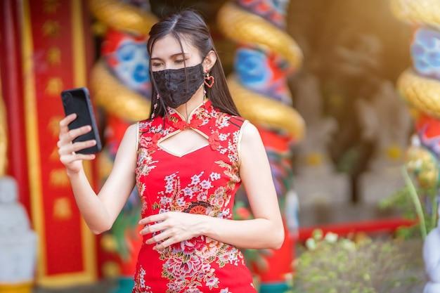 Azjatycka młoda kobieta ubrana w czerwony tradycyjny chiński cheongsam i nosi maskę ochronną i smartfon na obchody chińskiego nowego roku w sanktuarium, zapobieganie rozprzestrzenianiu się wirusa covid-19