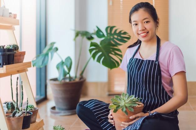 Azjatycka młoda kobieta ubrana w fartuch dba o zieloną roślinę w domu.