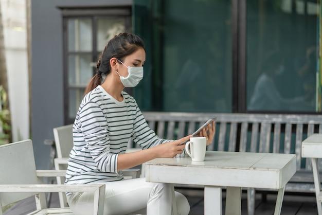 Azjatycka młoda kobieta ubrana w maskę medyczną za pomocą tabletu