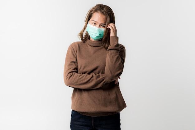 Azjatycka młoda kobieta ubrana w maskę ochronną na twarzy na białym tle, coronavirus covid-19