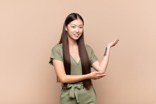Azjatycka młoda kobieta uśmiecha się dumnie i pewnie, czuje się szczęśliwa i usatysfakcjonowana oraz pokazuje koncepcję miejsca na kopię