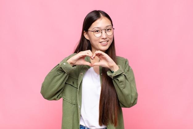 Azjatycka młoda kobieta uśmiecha się i czuje się szczęśliwa, słodka, romantyczna i zakochana, tworząc kształt serca obiema rękami