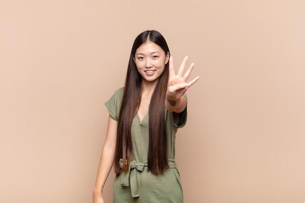 Azjatycka młoda kobieta uśmiecha się i wygląda przyjaźnie, pokazując numer cztery lub czwarty z ręką do przodu, odliczając w dół