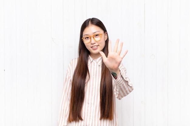 Azjatycka młoda kobieta uśmiecha się i wygląda przyjaźnie, pokazując numer pięć lub piąty z ręką do przodu, odliczając