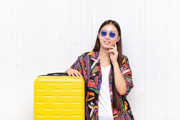 Azjatycka młoda kobieta uśmiecha się radośnie i marzy lub wątpi na białym tle