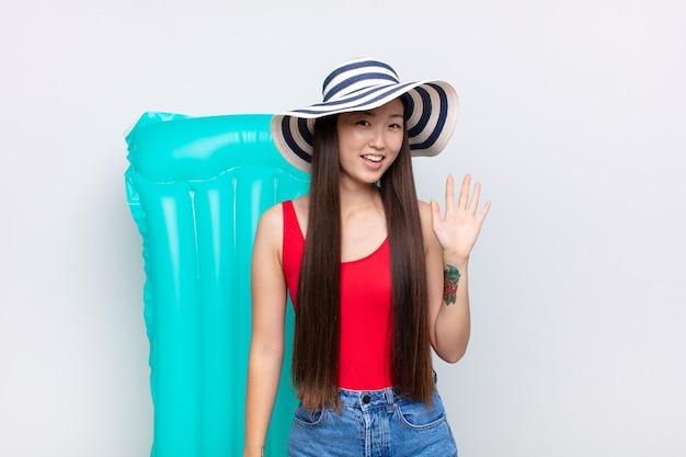 Azjatycka młoda kobieta uśmiecha się radośnie i wesoło, macha ręką, wita i wita lub żegna się. koncepcja lato