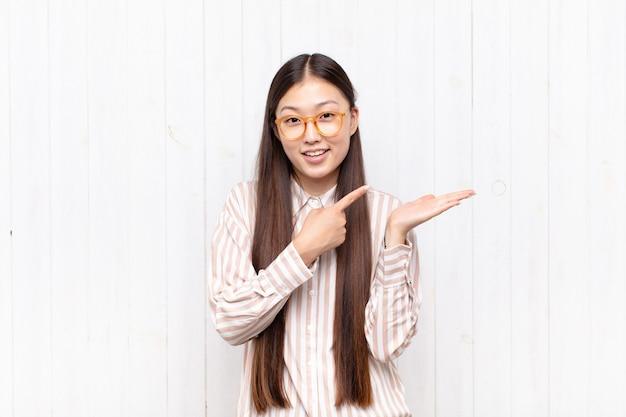 Azjatycka młoda kobieta uśmiecha się radośnie i wskazuje na kopiowanie miejsca na dłoni z boku, pokazując lub reklamując obiekt