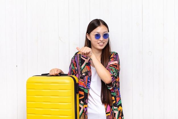 Azjatycka młoda kobieta uśmiecha się wesoło i niedbale, wskazując na bok