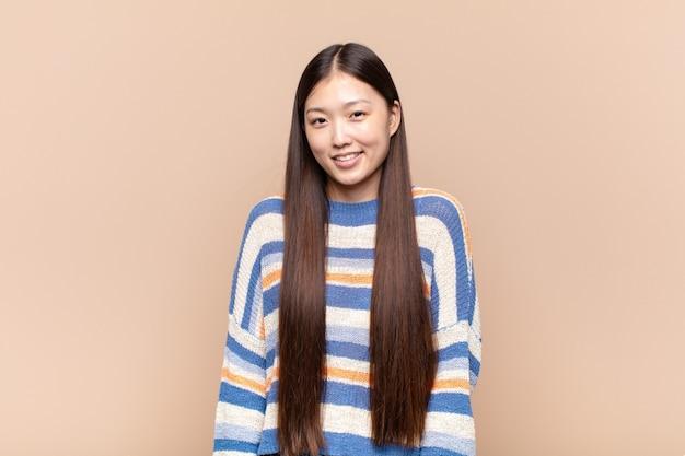 Azjatycka młoda kobieta uśmiecha się wesoło i niedbale z pozytywnym uśmiechem