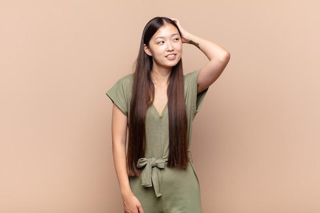 Azjatycka młoda kobieta uśmiecha się wesoło i niedbale